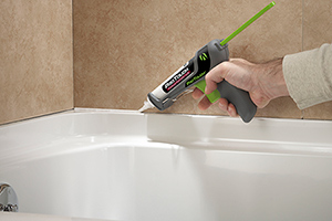 man caulked around the edge of a tub with the AdTech ProTouch Caulk System