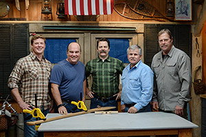 the cast of Ask This Old House stands around a table with Nick Offerman, who is holding a small wooden object