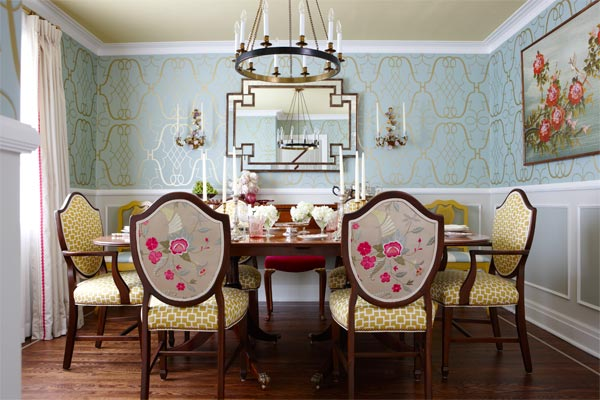 colorful, formal dining room with patterned blue and gold wall paper, and hanging candle chandelier over the decorated table. The table is surrounded by high back chairs with floral pattern on the back, and a gold, geometric pattern on the front and seats