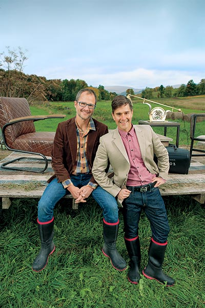 the designers Josh Kilmer-Purcell and Brent Ridge lean against a weathered wood platform  in an open green field. The platform behind them has a vintage looking chair and other objects that could be used in an interior
