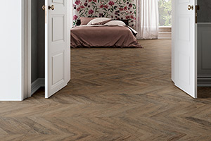 hallway and bedroom with Refin Ceramiche herringbone wood plank-style porcelain tile installed on the floor