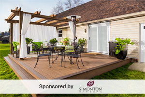 lovely wood deck with pergola on the far side attached to the back of a ranch style house. white curtains hang on either side of the pergola. outdoor furniture and potted plants rest on the deck.