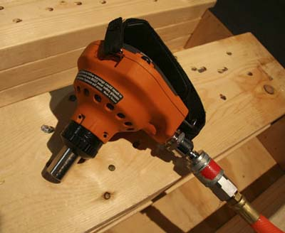 Rigid pneumatic palm nailer attached to compressor hose