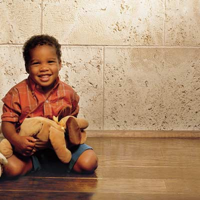 child with stuffed animal sitting on an engineered wood floor
