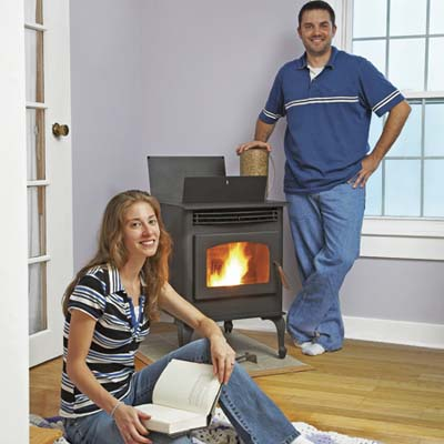 couple posing in a bare room with their pellet stove
