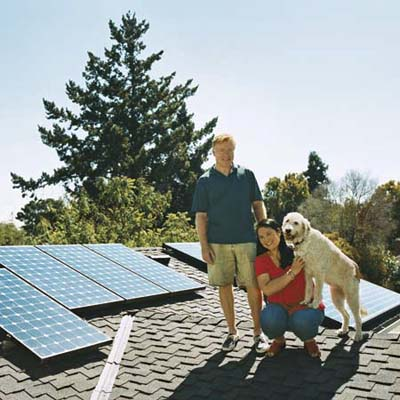 a couple and their dog stand on the roof ot their solar-paneled roof