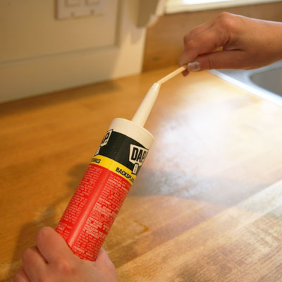 Chopsticks used to clean a tube of caulk