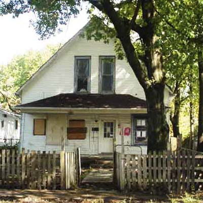 this 1895 2 bedroom sits on a small lot fronted by hardwood trees