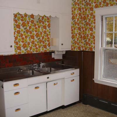 a kitchen before remodel with large floral print wallpaper