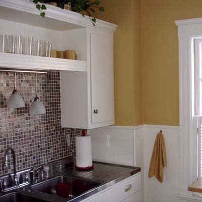 remodeled kitchen with newly painted walls, refurbished cabinets and new pendant lights