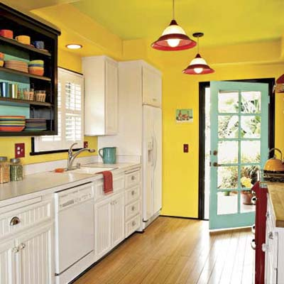 view of a kitchen in bright yellows and greens with a view to the door