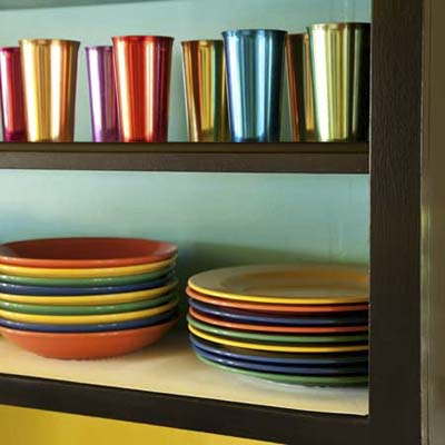 close up of painted open shelves displaying colorful plates and metal glasses