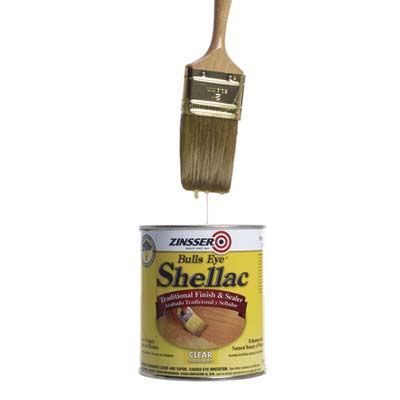 dripping paintbrush above a can of shellac