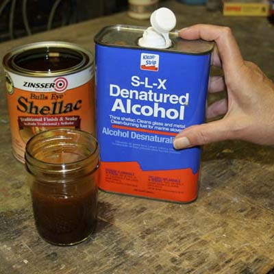small jar with mixture in front of can of shellac and hand on can of denatured alcohol