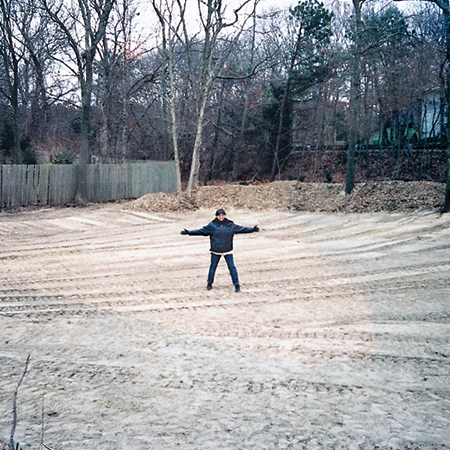 homeowner, Rosi Zingales stands in the middle of her regraded backyard