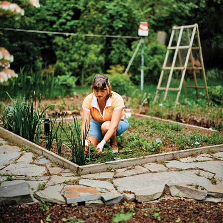 homeowner, Rosi Zingales kneeling in her vegetable garden