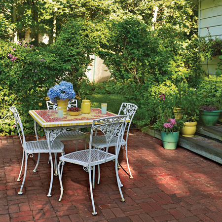 patio with restored iron table featuring Rosi's mosaic work