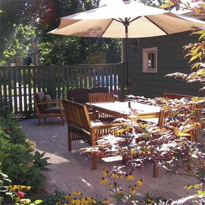 after photo of a back yard in Chicago, IL with stone patio and lush perennial garden