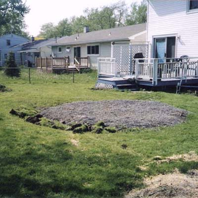 before photo of a back yard in Amherst, NY with large mound of gravel
