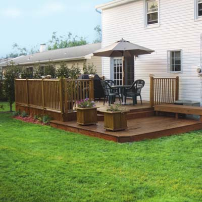 after photo of a back yard in Amherst, NY with new deck, flower boxes and a lush, green lawn