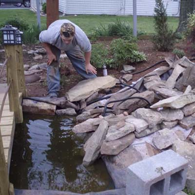 before photo of a back yard in Thurmond, MD with a developing pond on the side
