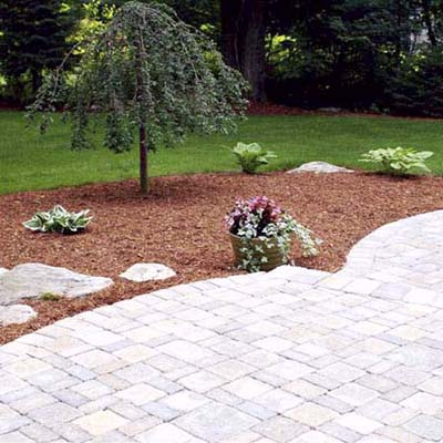 after photo of a back yard in Southborough, MA with stone patio and mulched garden