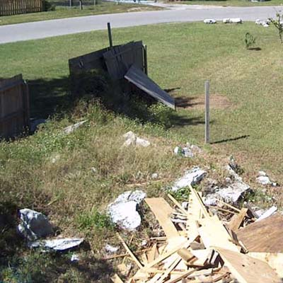 before photo of a back yard in Weeki Wachee, FL with a pile of debris in the foreground