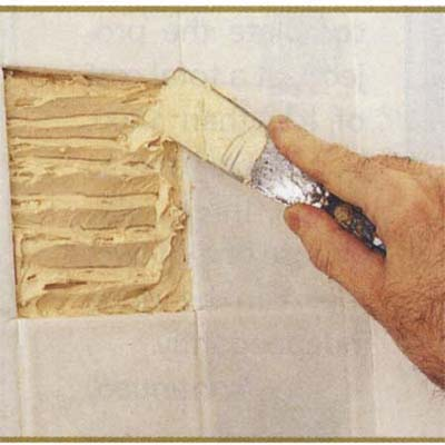 Applying tile adhesive with a putty knife
