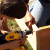 boy using a cordless driver to attach 2x10 cedar boards with deck screws