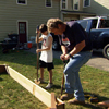 Roger Cook and young boy use edgers to mark out the perimeter of the raised bed