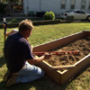 Roger Cook uses a 4-foot level to make sure the raised garden bed frame is level in the soil
