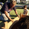 Roger Cook reattaches the last board of the raised garden bed frame
