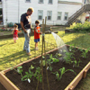 Roger Cook supervises as a young boy waters the soil in the raised garden bed
