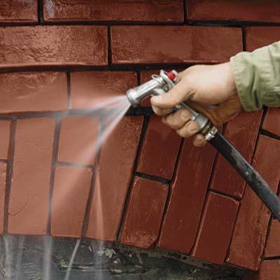 washing away mortar debris from a brick wall