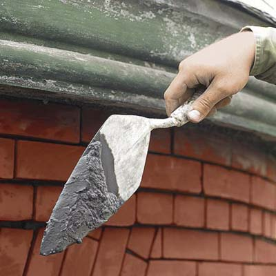 mixing mortar to apply to a brick wall