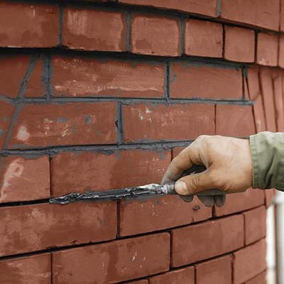 filling the brick wall joints with mortar