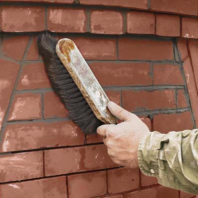 brushing a brick wall to remove mortar crumbs