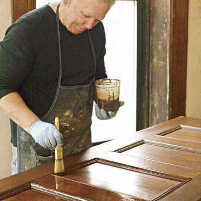 John Thomas brushes on a final coat of satin spar varnish