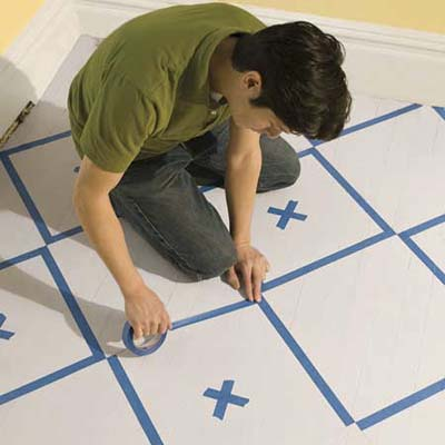 masking the checker pattern on a floor with painter's tape
