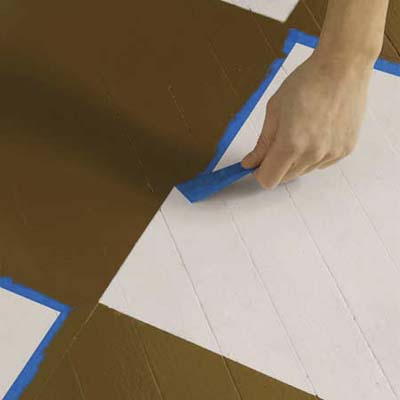 removing the painter's tape from a checkerboard-painted wood floor