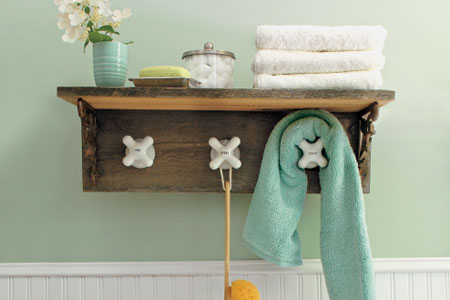 completed towel rack made from vintage taps with shelf installed in a green bathroom