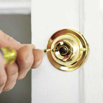 man reattaching a doorbell button