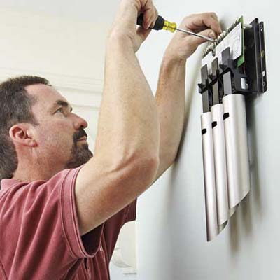man replacing an electrical doorbell chime