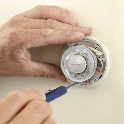 person unscrewing an old thermostat in order to remove it