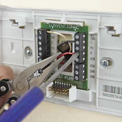 connecting wires to a new thermostat using needlenose pliers and a screwdriver