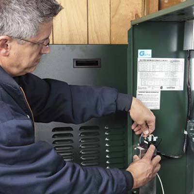 Lance Marques connects the thermostat power wire to the furnace