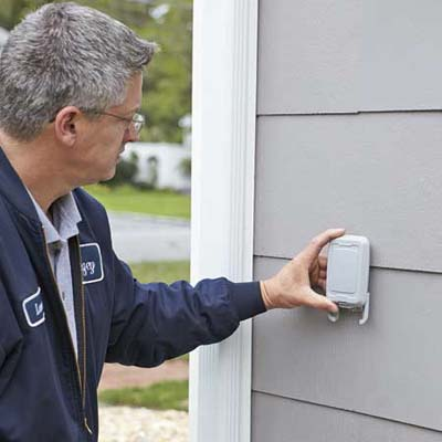 Lance Marques mounts the outdoor sensor that allows the thermostat to measure the temperature outside