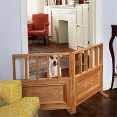 small dog standing up on a dog gate set up between two rooms
