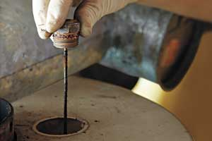 a latex-gloved hand lifts an anode rod that is way overdue for replacement from a water heater
