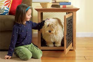 little girl petting a dog in a pet crate that doubles as a side table